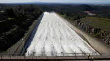 """In this Saturday, Feb. 11, 2017, photo, water flows down Oroville Dam's main spillway, in Oroville, Calif. Officials have ordered residents near the Oroville Dam in Northern California to evacuate the area Sunday, Feb. 12, saying a """"hazardous situation is developing"""" after an emergency spillway severely eroded. (AP Photo/Rich Pedroncelli)"""