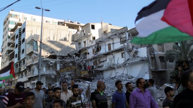 Palestinians hold a Palestinian flag and walk past a building destroyed by Israeli air strikes in the northern Gaza Strip as they take part in a protest at the Jerusalem Day flag march (15 June 2021)